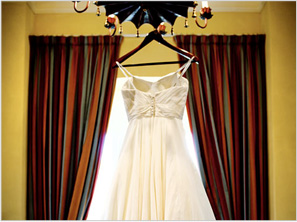 wedding dress hanging by a window